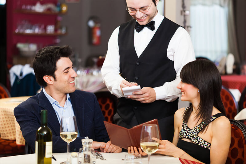 A restaurant's waiter takes the order of customers to increase the revenue of the food business