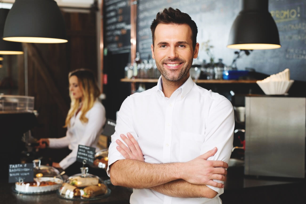A cafe entrepreneur smiles in his successful food business.